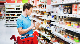 Man stands in a grocery aisle contemplating item in hand